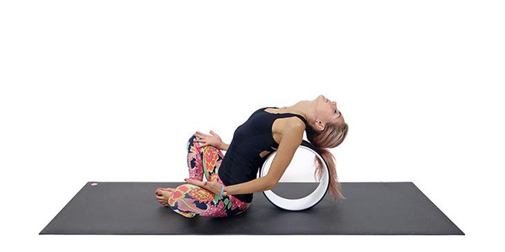 Поза бабочки на колесе для йоги